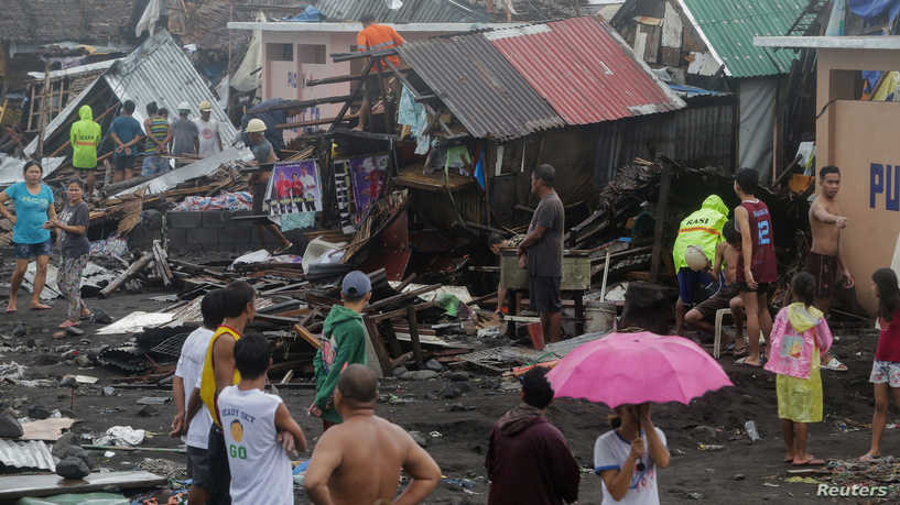 Residents stand among their damaged houses after Typhoon Kammuri hit Legazpi City, Albay